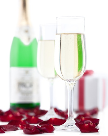 Two glasses of champagne, gift box, rose petals on white background. photo