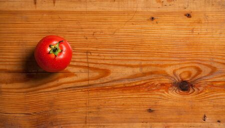One ripe tomato on a decorative board