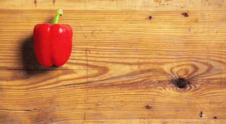 One sweet red peppers on a decorative board.