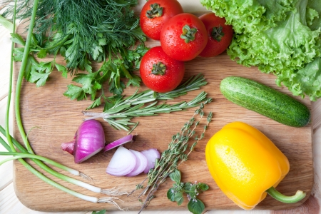Fresh vegetables, herbs and spices on a cutting board