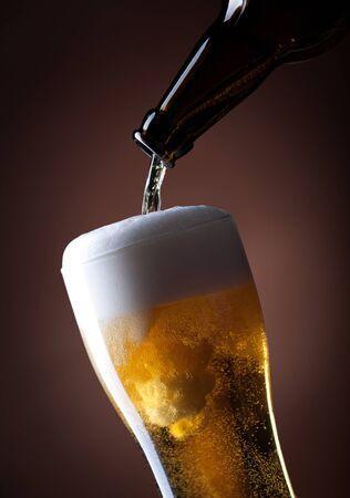cerveza negra: cerveza y una botella de vidrio sobre un fondo marrón
