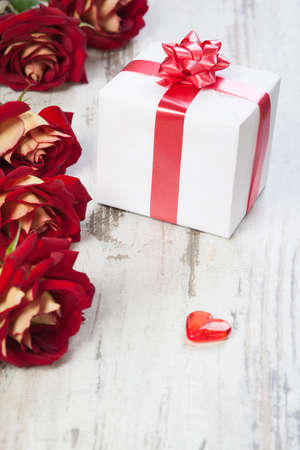 gift box with red ribbon on a white board with roses