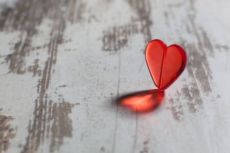 plastic heart: red plastic heart on a white board with a beautiful shadow