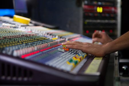 Soundman working on the mixing console  Hands on the sliders