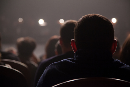 Spectators wait for the start of the concert sitting in the chairs in the auditorium  photo