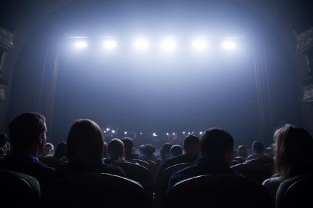 관중은 강당에 의자에 앉아 콘서트의 시작을 기다립니다 스톡 콘텐츠