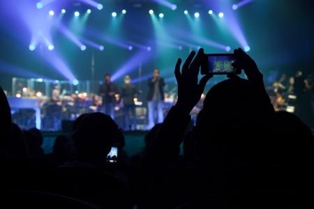 Toeschouwers nemen foto's van acteurs uit het publiek op een mobiele telefoon tijdens de uitvoering Stockfoto