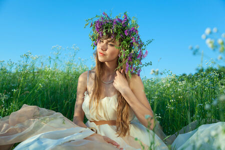 Young girl sitting in amongst the flowers and grass in the field. photo