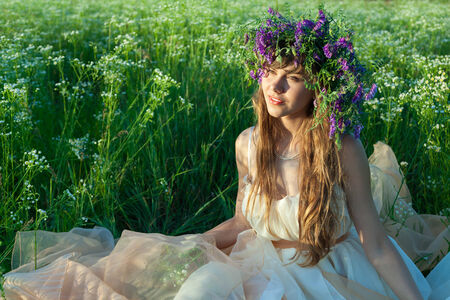 Young girl sitting in amongst the flowers and grass in the field. Stock Photo