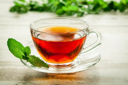 Kopje thee met munt op bladeren houten tafel. Stockfoto