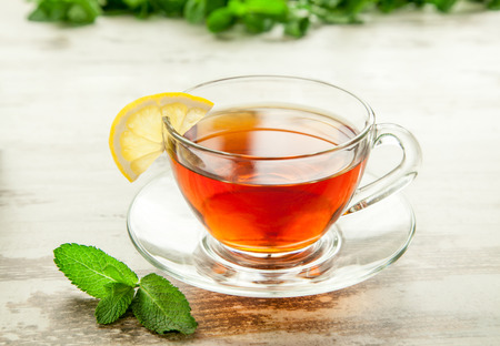 Glass cup of tea on a wooden table with lemon and mint leaves.