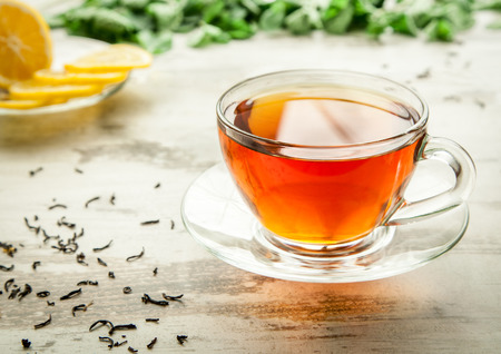 Glass cup of tea on a wooden table with sliced lemon. Stock Photo