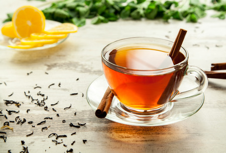 Glass cup of tea on a wooden table with sliced lemon and cinnamon.