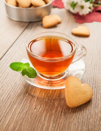 Glass cup of tea on a wooden table with flowers and a box of cookies.