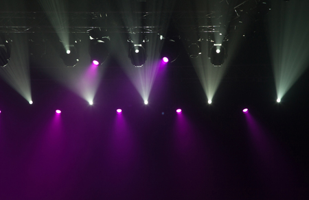 holiday lighting: Stage lights on concert. Lighting equipment with multi-colored beams.