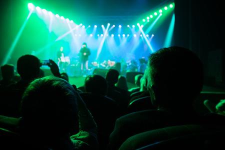 Het publiek bij een concert op de achtergrond van scene.