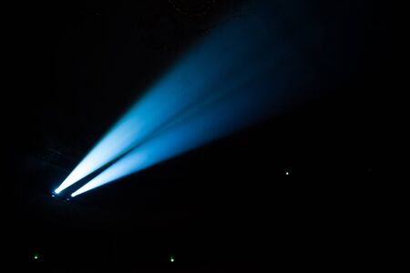 searchlights: Two beams of searchlights in the dark concert hall.