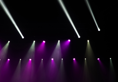 burgundy colour: Stage lights on concert. Lighting equipment with multicolored beams.