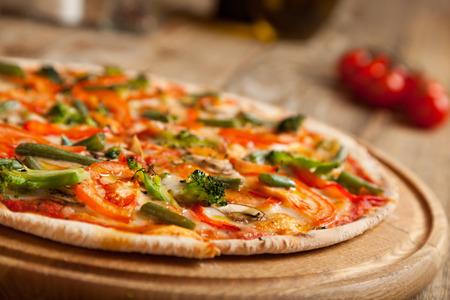 """pizza: Pizza italiana """"Vegetariano"""" en la mesa de madera. En la parte superior de la pizza son los tomates en rodajas al horno y br�coli esp�rragos. Muy cerca se encuentran los contenedores con especias y aceite de oliva. Cerca de ellos son los tomates cherry."""