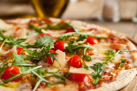 """Italiaanse pizza """"Caprese"""" ligt op mooie houten tafel. Op de top van een pizza gesneden, gebakken cherry tomaten, rucola en Parmezaanse kaas plakjes. In de omgeving zijn de containers met kruiden en olijfolie."""