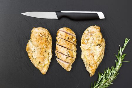 Ready chicken on the old plastic cutting board. Stock Photo