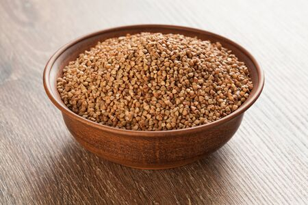 Full ceramic bowl with buckwheat on wooden background.