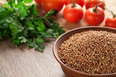 Composition with ceramic bowl dry buckwheat, tomatoes and parsley in the background. Stock Photo