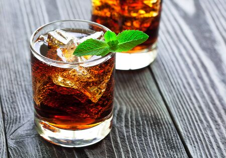 Two glasses of cola with ice and fresh mint on a beautiful wooden table.