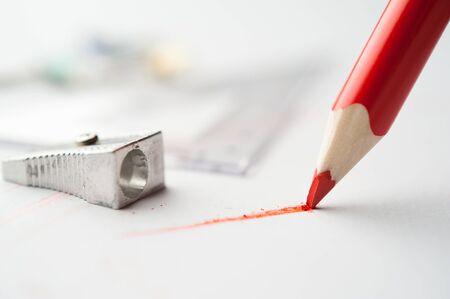 Rood potlood schrijft op papier.