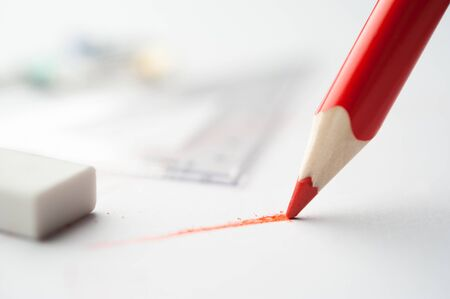 red pencil: Red pencil writes on paper.