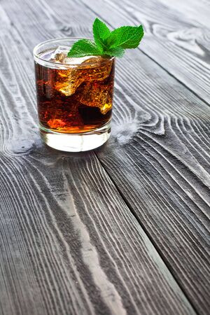 Glass of cola with ice and  fresh mint on a beautiful wooden table.