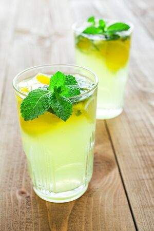 Two glasses of drink with lemon and fresh mint on a beautiful wooden table.