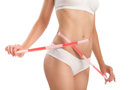 slim tummy: Slim body of woman with a measuring tape.