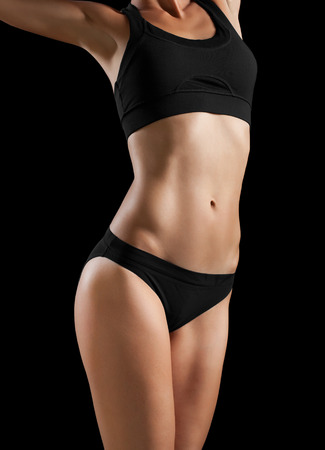 slim tummy: Slim body of woman isolated on black. Stock Photo