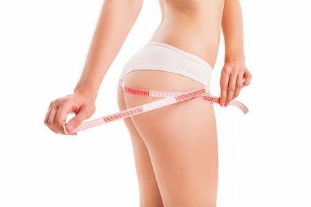 cuerpo perfecto femenino: Slim cuerpo de mujer con una cinta métrica. Foto de archivo