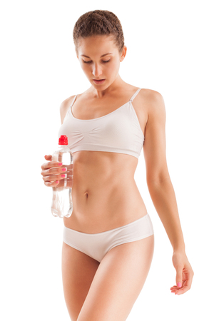girl care: Slim athletic girl with bottle of water in hand isolated on white. Stock Photo
