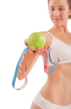 cuerpo femenino perfecto: Muchacha atractiva con la manzana verde y cinta m�trica en la mano.