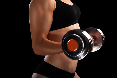 Athletic girl with dumbbells in hand isolated on black.