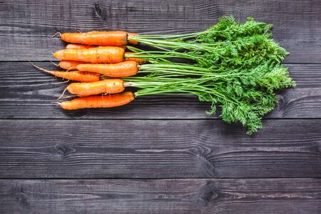 Ripe fresh carrots on a wooden background black color.