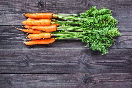 zanahoria: zanahorias frescas maduras sobre un fondo de madera de color negro.