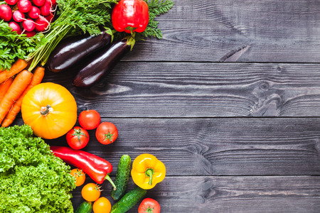 Background of wooden planks black color with fresh vegetables. 스톡 콘텐츠