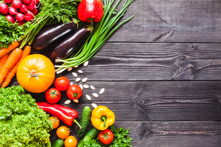 Background of wooden planks black color with fresh vegetables. Stock Photo