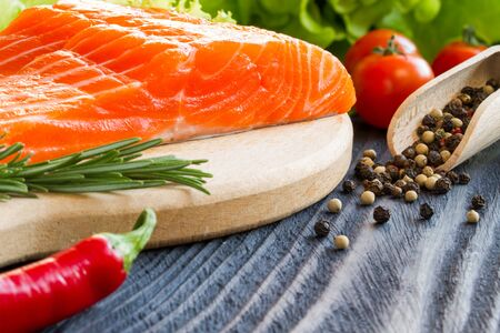 seasonings: Fresh raw salmon fillet on cutting board with seasonings. Stock Photo