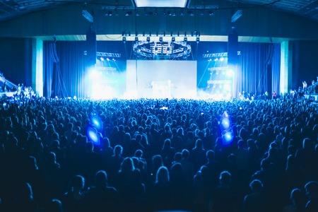 Grote concertzaal gevuld met toeschouwers voor het podium.