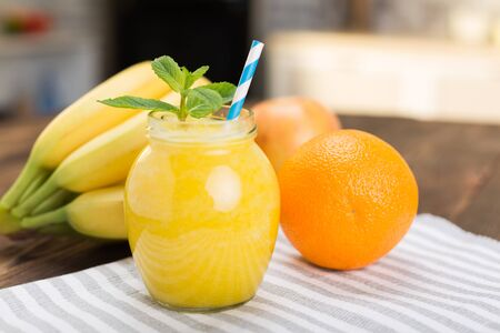 Fresh fruit smoothies on kitchen table in a small jar