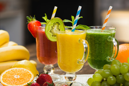 Fresh fruit and vegetable smoothie on kitchen table in glass Stock Photo