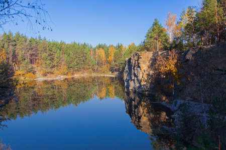 Fragment of the lake shore with a stone in autumn forest in early morning Stock Photo