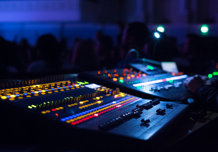 Soundman working on the mixing console in concert hall. Hands on the sliders. Reklamní fotografie