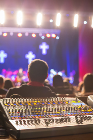 Work place sound engineers in concert hall. Mixing console. Stock Photo