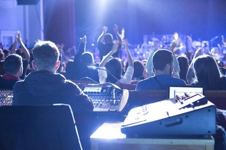 Geluidsman aan het mengpaneel in de concertzaal.